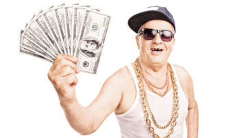 Toothless old man in hip-hop outfit holding a pile of cash isolated on white background