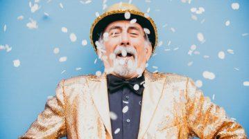 Starszy mężczyzna ubrany w złoty garnitur i melonik wie ile kosztuje szczęście