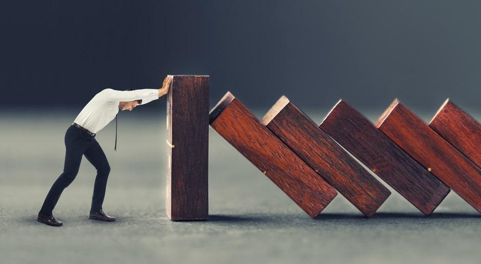 Jak przygotować się na kryzys finansowy? - mężczyzna trzymający domino